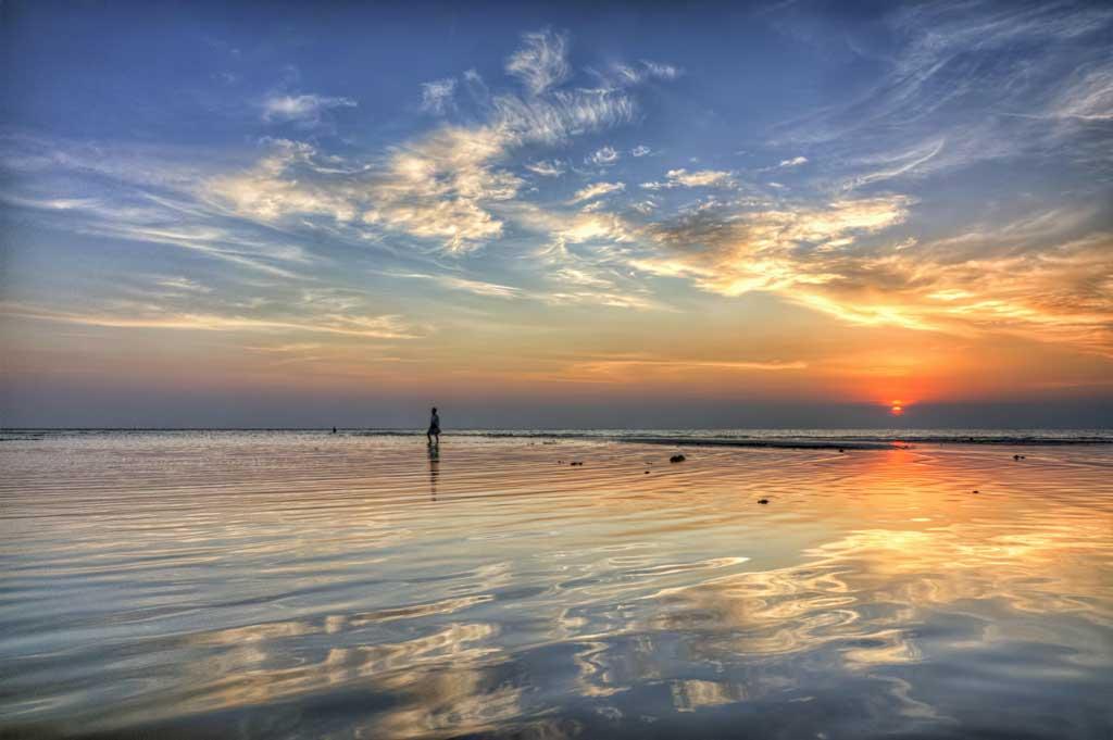 Eine Person erlebt einen Sonnenuntergang am Meer und lernt Gott kennen